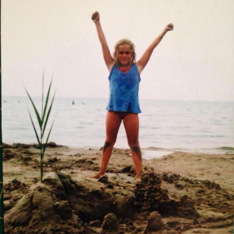 Petite fille les pieds dans le sable, sur le bord de la place.